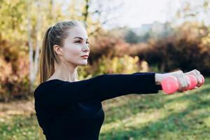 mulher feliz fitness treinando com halteres ao ar livre. garota levantando pesos livres no verão. foto
