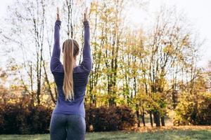 mulher na floresta vista traseira jovem mulher atraente de atividade ao ar livre fazendo exercício trabalhando ao ar livre. visão traseira foto