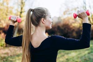 mulher bonita malhando ao ar livre. mulher esportiva treinando com halteres, vista traseira foto