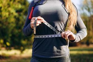 mulher atlética e magra medindo a cintura com fita métrica após treino ao ar livre foto