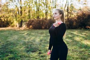 garota atlética fazendo fitness ao ar livre com halteres, vista lateral. foto