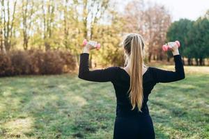 aptidão no parque, garota segurando halteres, vista traseira. foto
