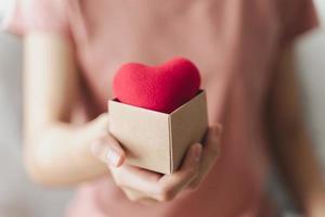 mulher segurando uma caixa de presente com coração vermelho, amor, seguro de saúde, doação, voluntário de caridade feliz, dia mundial da saúde mental, dia mundial do coração, dia dos namorados foto