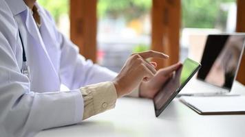 um homem com uma bata de laboratório está segurando e operando um tablet, um profissional médico com uma bata de laboratório está usando um tablet, foto lateral.