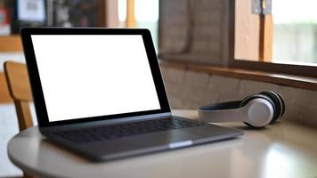 tela em branco do laptop maquete e fone de ouvido colocado sobre uma mesa em um café. foto