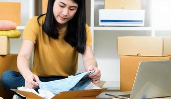 mulher embala uma camisa em uma caixa de pacote para entrega a um cliente, vende produtos online, transporta pacotes. foto