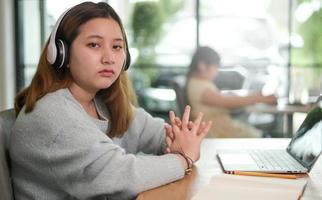 jovens estudantes do sexo feminino descansam enquanto usam laptops para estudar online, a garota parece exausta. foto