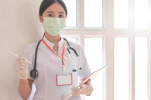 uma médica usando uma máscara segura um arquivo do paciente com o estetoscópio. foto