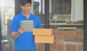 o mensageiro segurando uma caixa de pacote está usando um tablet para verificar o endereço do cliente. foto