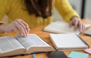 close-up tiro de mulheres jovens vestindo roupas amarelas estão lendo livros para se preparar para o vestibular. foto