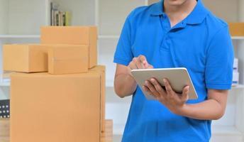 o mensageiro está usando um tablet para registrar as informações de entrega. foto