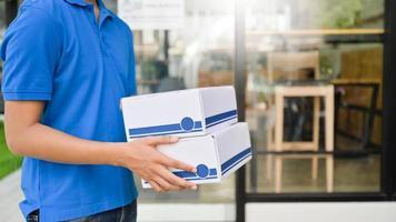 o oficial entrega o pacote para a casa do cliente. foto