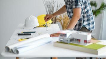 o desenhista está desenhando a planta da casa, casas modelo e plantas da casa com um capacete de segurança na mesa. foto