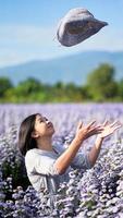 mulher asiática feliz posando em um jardim de flores e jogando um chapéu enquanto tirava a foto. foto