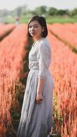 mulher asiática feliz andando e tirando fotos no jardim de flores.