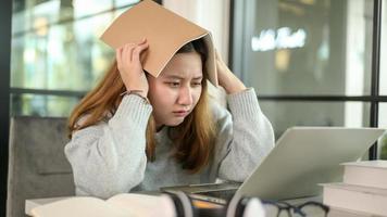 adolescente asiática segurando um livro na cabeça estressada olhando para o laptop durante as aulas online do laptop. foto