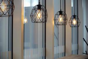 lâmpadas de carcaça de metal preto de café moderno perto de janelas foto