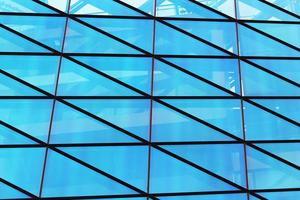 parede da janela de vidro de um edifício moderno com reflexo do céu azul foto