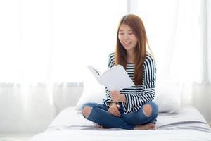 linda de uma jovem mulher asiática relaxar sentado lendo um livro no quarto. foto