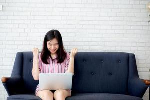 jovem mulher asiática, animada e feliz com o sucesso com o laptop no sofá. foto