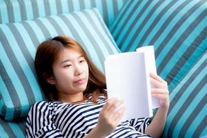 jovem mulher asiática relaxar deitado lendo livro no sofá. foto
