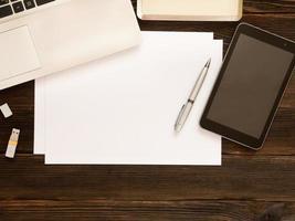 folhas brancas de papel, caneta, tablet, caderno, cartão de memória USB e outros itens em fundo escuro de madeira. conceito de negócios. espaço livre para texto foto