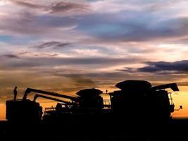 silhueta de colheitadeiras descarregando soja em um caminhão ao pôr do sol, durante a colheita de uma fazenda no brasil foto