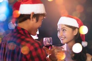 contato visual de amantes asiáticos olhando e sorrindo um para o outro no bar. conceito de lua de mel e férias foto