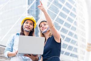 duas mulheres pesquisando engenharia para inicialização e lançamento de novo projeto. edifício e conceito de construção. negócios e felicidade do conceito de cooperação. tema engenheiro civil. cidade e tema urbano foto