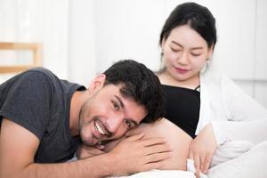 pai ouvindo o filho chutando o som dentro da barriga da mãe quando está sentado na cama em casa. conceito de família e amantes. feliz doce lar e tema de casamento foto