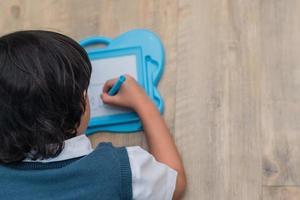 menino desenhando esboço na prancheta na escola em casa. educação e de volta ao conceito de escola. tema de desenvolvimento infantil. vista do topo foto