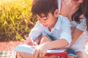 garotinho asiático e sua mãe lendo livros de contos no campo Prado. mãe e filho aprendendo juntos. comemorando no dia das mães e apreciando o conceito. pessoas de verão e educação de estilo de vida foto