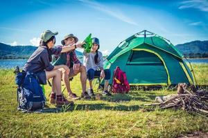 grupo de jovens amigos asiáticos faz um piquenique e festa no lago com mochila de camping e cadeira. jovens brindando e torcendo por garrafas de cerveja. conceito de pessoas e estilos de vida. tema de fundo ao ar livre foto