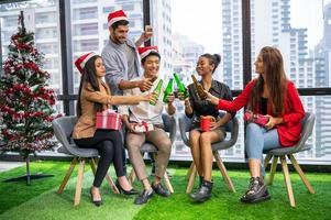 grupo de negócios diversidade colega trabalho em equipe celebaring para festa de ano novo no fundo do escritório urbano moderno. amigos se divertindo com uma festa com álcool e bebem juntos. multi-ética pessoas estilo de vida foto