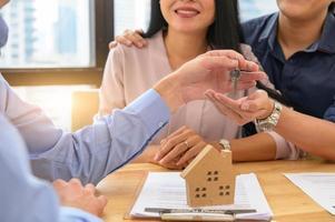 o corretor de imóveis oferece uma casa particular para o cliente antes de assinar os documentos do contrato de propriedade da casa de aluguel. compra de propriedade imobiliária. conceito de aprovação de empréstimo hipotecário. investimento de dinheiro foto