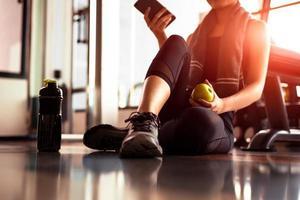 close-up de mulher usando telefone inteligente e segurando a maçã enquanto treino no ginásio de fitness. conceito de esporte e tecnologia. estilo de vida e tema de saúde foto
