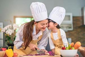 feliz menino fofo com óculos beijando a mãe linda mulher asiática enquanto se prepara para cozinhar na cozinha em casa. pessoas estilos de vida e família. conceito de comida e ingredientes caseiros foto