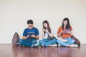 grupo de estudante universitário asiático usando tablet e celular fora da sala de aula. felicidade e conceito de aprendizagem de educação. de volta ao conceito de escola. tema adolescente e pessoas. ar livre e tema de tecnologia foto