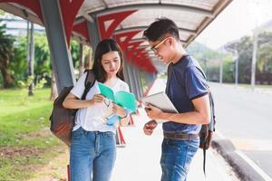 dois jovens universitários asiáticos discutindo sobre a leitura de um livro e usando o laptop para pesquisar e aprender conhecimento. conceito de educação e amizade. felicidade e conceito de aprendizagem. amantes e amigo tema foto