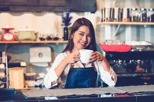 asiático feminino barista fazendo café. jovem segurando a xícara de café branca em pé atrás do balcão do café no fundo do restaurante. estilo de vida das pessoas e conceito de ocupação de negócios foto