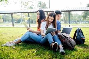 grupo de estudante universitário asiático usando tablet e laptop em campo de grama ao ar livre. conceito de aprendizagem de tecnologia e educação. tecnologia futura e conceito de entretenimento moderno. tema edutainment foto