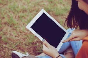 mulher asiática de beleza usando tablet no parque. pessoas e conceito de tecnologia. tema de lazer e atividades ao ar livre foto