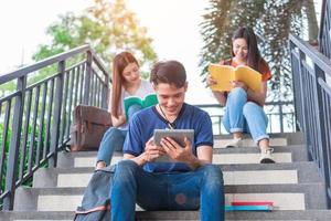 grupo de estudante universitário asiático lendo e revisando por livro didático e laptop na escada na Universidade. conceito de aprendizagem de tecnologia e educação. tema de entretenimento e educação e entretenimento foto