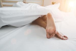 com os pés descalços de um humano na cama pela manhã. conceito de pessoas solteiras e trabalhadoras. tema de casa de dia preguiçoso e felicidade foto