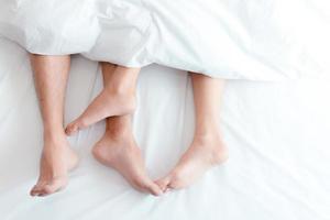 closeup pés de casal na cama. os amantes do homem e da mulher fazem amor debaixo do cobertor ou do lençol. sexo no tema das férias. conceito de dia dos namorados e lua de mel foto