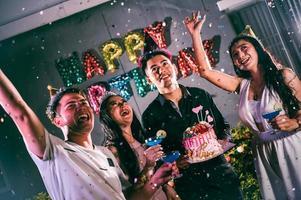 amigos asiáticos se divertindo na festa de aniversário na boate com bolo de aniversário. conceito de evento e aniversário. pessoas estilos de vida e amizade foto
