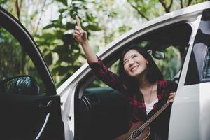 mulher asiática de beleza apontando e se divertindo no verão ao ar livre com ukulele no carro branco. viagem do conceito de fotógrafo. estilo moderno e tema de mulher solo. estilo de vida e tema de vida de felicidade foto