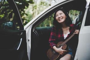 mulher asiática de beleza sorrindo e se divertindo no verão ao ar livre com ukulele no carro branco. viagem do conceito de fotógrafo. estilo moderno e tema de mulher solo. estilo de vida e tema de vida de felicidade foto