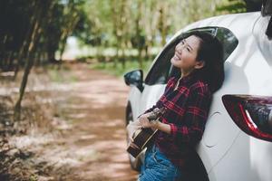 mulher asiática de beleza sorrindo e se divertindo no verão ao ar livre com ukulele perto de carro branco. viagem do conceito de fotógrafo. estilo moderno e tema de mulher solo. estilo de vida e tema de vida de felicidade foto