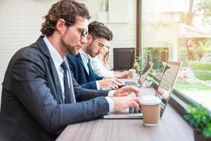 grupo de empresários que trabalham com laptops modernos no escritório. conceito de trabalho em equipe e cooperação. trabalhador de negócios e tema de homem de salário. tema inovador e tecnológico foto